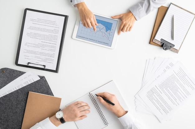 Flache anordnung der hände von zwei jungen managern oder maklern, die online-finanzinformationen analysieren und planpunkte oder neue ideen aufschreiben