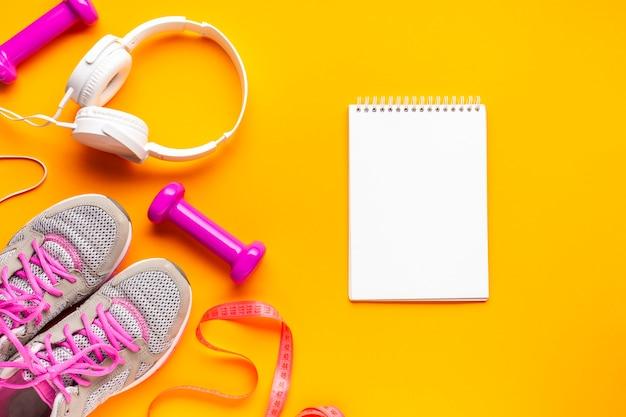 Flache anordnung mit sportattributen und notizbuch