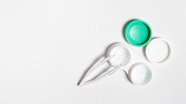 Flache auflage eines transparenten kontaktlinsenbehälters mit pinzette und platz für text
