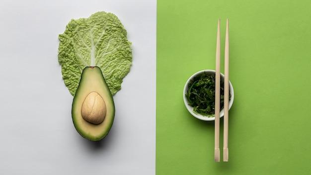 Flache avocado mit schüssel mit gemüse und stäbchen