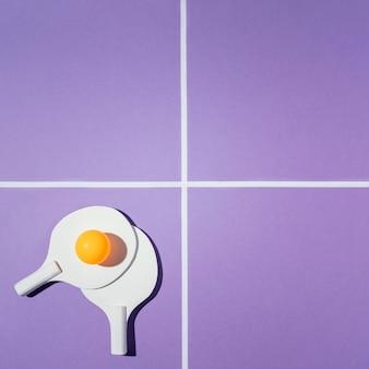 Flache badmintonpaddel auf lila hintergrund legen