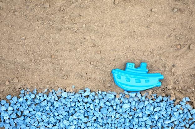 Flache blaue kieselsteine mit boot auf sand legen