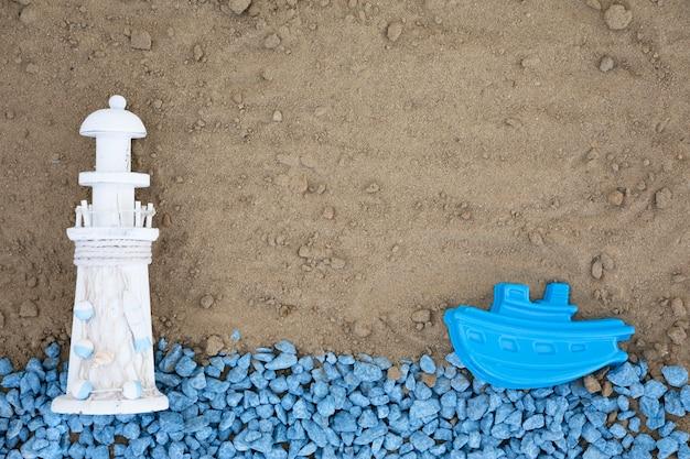 Flache blaue kieselsteine mit leuchtturm und boot auf sand legen
