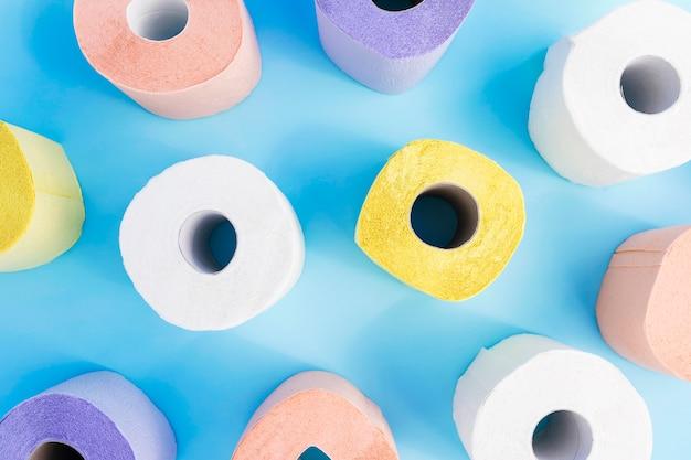Flache bunte toilettenpapierrollen auf schreibtisch legen