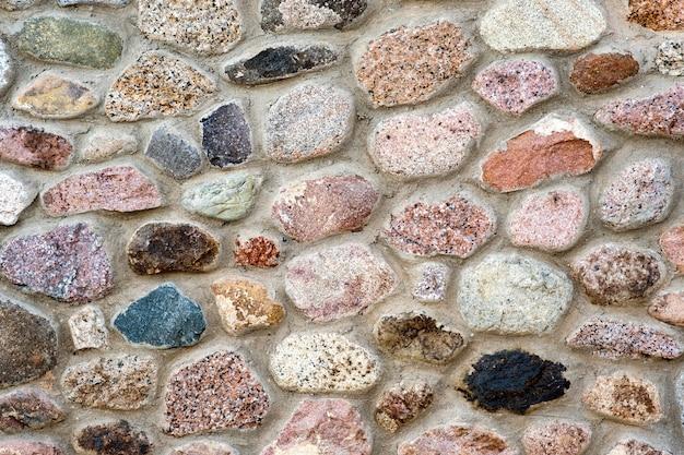 Flache detailansicht einer wand aus verschiedenen steinen. abstrakter steinhintergrund.