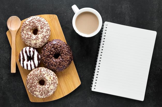Flache donuts auf schneidebrett mit notizbuch und kaffee