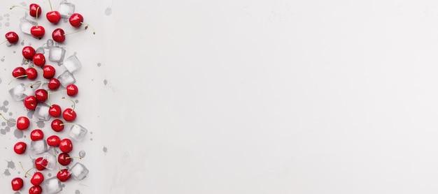 Flache draufsicht auf grauem betonhintergrund mit süßen kirschbeeren und eiswürfeln. frische, sommer konzeptioneller minimaler hintergrund. öko-, bio-bauernhof-lebensmittel- und obstkonzept mit kopierbereich