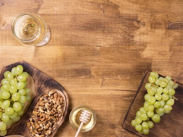 Flache draufsicht auf honigglas neben frischen trauben auf holztisch. jahrgang weißwein. essen probieren. kopieren sie platz zur verfügung.