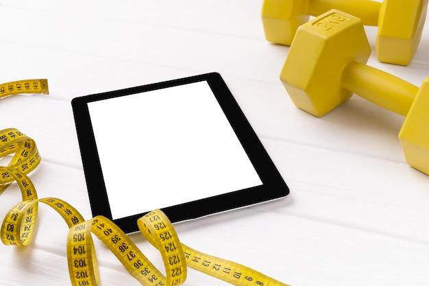 Flache draufsicht auf tablette mit gelben sportgeräten auf weißem hölzernem hintergrund. online-fitnesskonzept für einen gesunden lebensstil