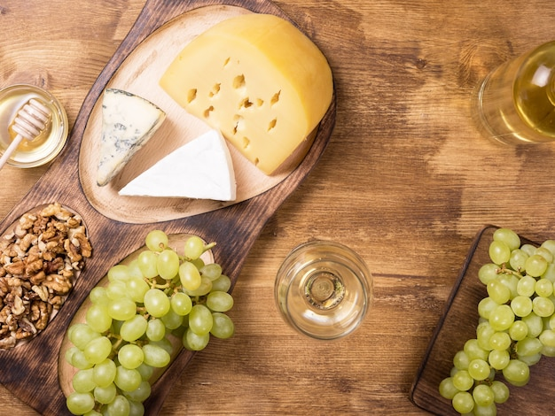 Flache draufsicht auf verschiedene käsesorten neben frischen trauben, glas wein auf einem holztisch. kopieren sie platz zur verfügung.
