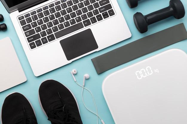 Flache draufsicht des laptops mit sportausrüstungen auf blauem hintergrund.