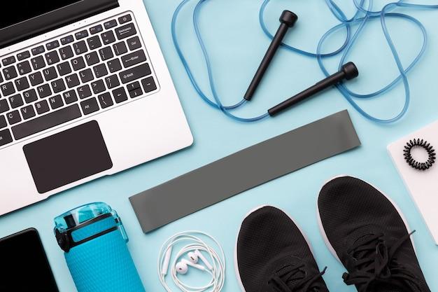 Flache draufsicht des laptops mit sportausrüstungen auf blauer oberfläche
