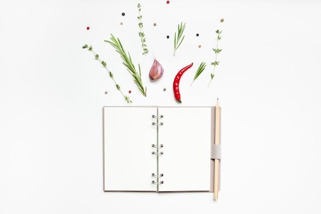 Flache draufsicht leere notizbuchseiten mockup textraum einladungskarte auf weißem hintergrund mit grünen kräutern und gewürzen. menü- oder rezeptbuch- oder food-blog-design mit kochzutaten