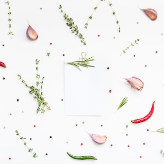 Flache draufsicht leere rezeptpapierseite mit clip-mockup-textraum-einladungskarte auf weißem hintergrund mit grünen kräutern und gewürzen. menü-rezeptbuch-food-blog-design mit kochzutaten
