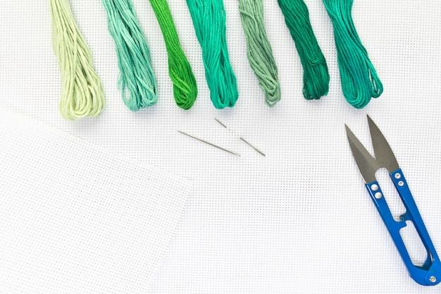 Flache draufsicht mit stickerei-leinwand, nadeln, fäden in grünen farben