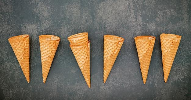 Flache eistüten-sammlung auf dunklem steinhintergrund. leere knusprige eistüte mit kopienraum für süßigkeiten-menü-design.