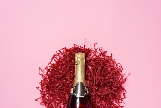 Flache feier. sektflasche mit bunten party-streamern auf rosa hintergrund.