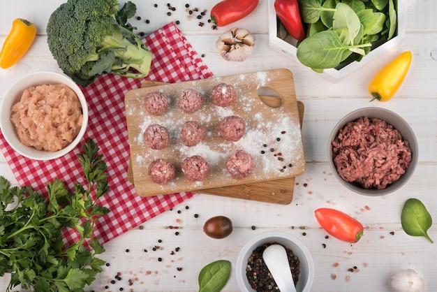 Flache fleischbällchen auf holzbrett, hackfleisch und broccoli legen