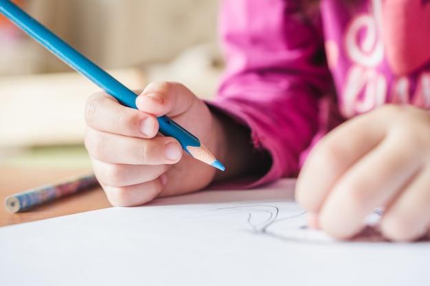 Flache fokusansicht eines kindes, das ein rosa t-shirt trägt, das ein bild mit dem blauen buntstift malt