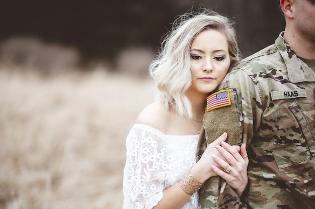 Flache fokusaufnahme einer attraktiven frau, die den arm eines amerikanischen soldaten hält
