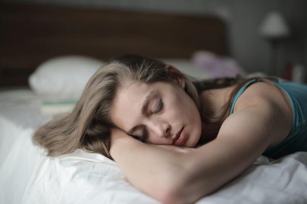 Flache fokusaufnahme einer frau, die auf ihrem bett schläft