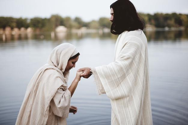 Flache fokusaufnahme einer frau, die ein biblisches gewand trägt, während sie die hand jesu christi hält holding