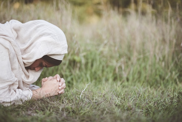 Flache fokusaufnahme einer frau unten auf dem boden, die betet, während sie ein biblisches gewand trägt
