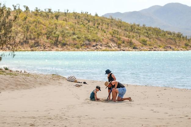Flache fokusaufnahme einer glücklichen familie, die sich am sandstrand entspannt