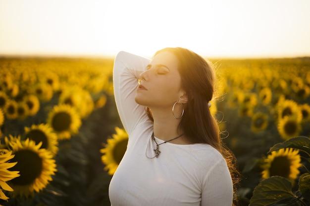 Flache fokusaufnahme einer hübschen europäischen frau in einem sonnenblumenfeld bei sonnenaufgang