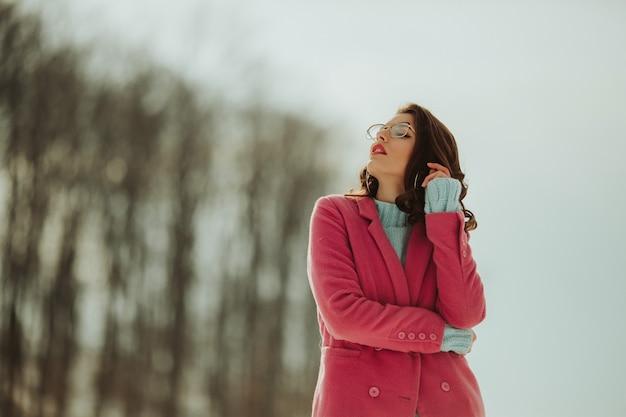 Flache fokusaufnahme einer schönen kaukasischen frau, die bei tageslicht auf einem schneebedeckten feld posiert