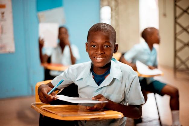 Flache fokusaufnahme eines afrikanischen kindes, das in der schule lernt