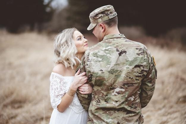 Flache fokusaufnahme eines amerikanischen soldaten mit seiner liebenden frau, die auf einem feld steht