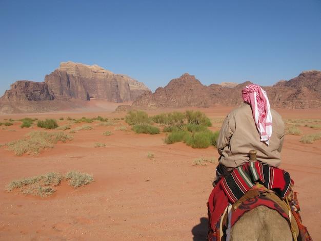 Flache fokusaufnahme eines arabischen mannes, der auf einem pferd in einer wüste reist