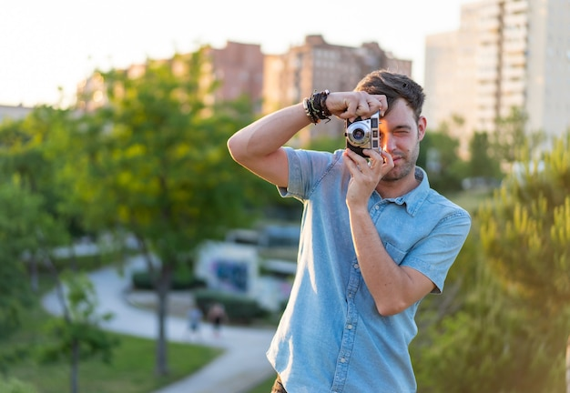 Flache fokusaufnahme eines jungen mannes, der ein foto im park macht