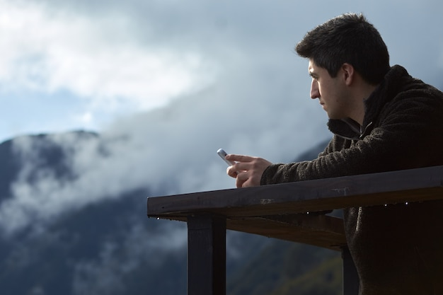 Flache fokusaufnahme eines jungen mannes mit seinem smartphone