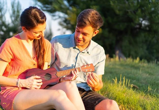 Flache fokusaufnahme eines jungen paares, das im park ukulele spielt