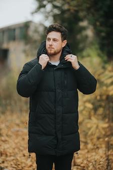 Flache fokusaufnahme eines jungen und attraktiven mannes, der vor der kamera posiert