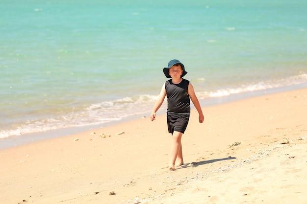 Flache fokusaufnahme eines kleinen jungen mit hut, der am sandstrand spazieren geht