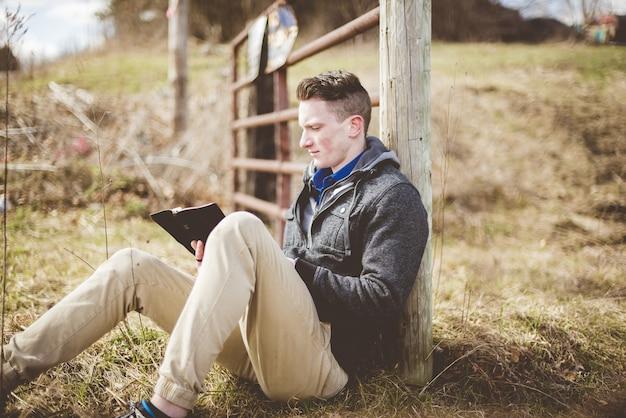 Flache fokusaufnahme eines mannes, der auf dem boden sitzt, während er die bibel liest