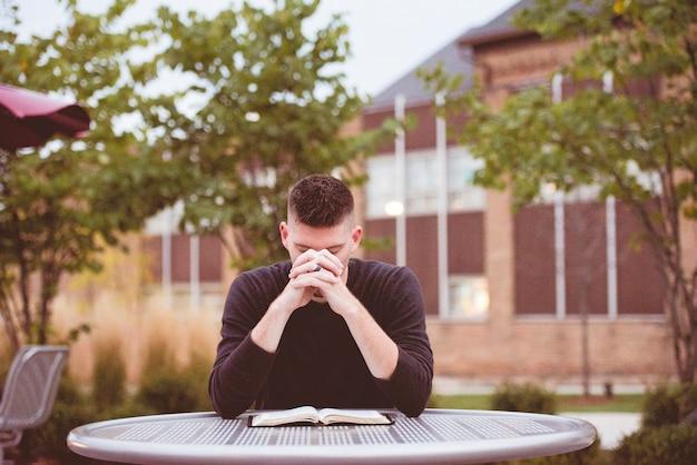 Flache fokusaufnahme eines mannes, der mit einer offenen bibel betet