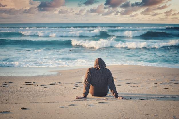 Flache fokusaufnahme eines mannes in einer schwarzen jacke, der an einem sandstrand sitzt