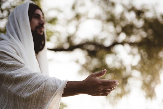 Flache fokusaufnahme von jesus christus, der eine helfende hand reicht