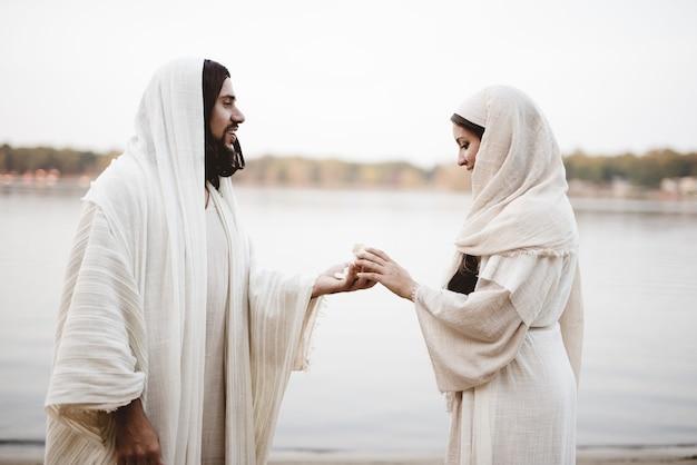 Flache fokusaufnahme von jesus christus, der einer frau, die ein biblisches gewand trägt, ein stück brot gibt