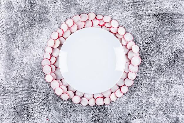 Flache gehackte rote radieschen in weiße platte legen