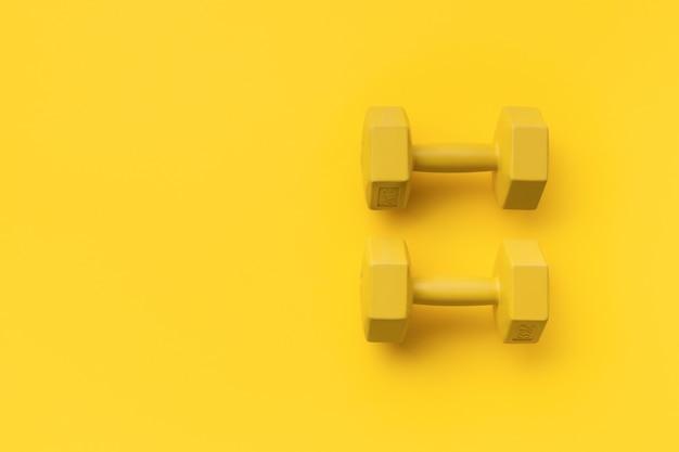 Flache gelbe sportausrüstung auf gelber oberfläche mit kopierraum