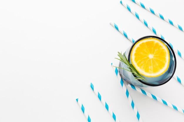 Flache glaslage mit zitronenscheibe und erfrischungsgetränk