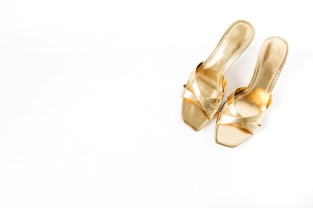 Flache goldene damenschuhe auf weißem leinen