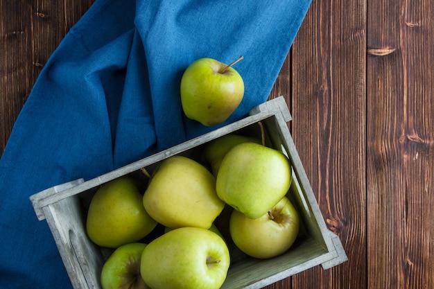Flache grüne äpfel in der holzkiste auf blauem stoff und hölzernem hintergrund legen. horizontal