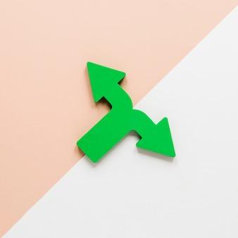 Flache grüne pfeile und cremefarbener karton auf weißem hintergrund