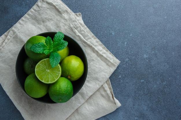 Flache grüne zitronen und blätter in der schwarzen schüssel auf weißem stoff auf dunklem hintergrund legen. horizontal